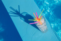 El vidrio con hielo y la paja hielan cerca de la piscina Fotografía de archivo libre de regalías