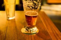 El vidrio de ámbar delicioso bebido cerveza espumosa se coloca imagenes de archivo