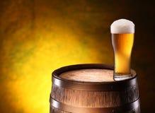 El vidrio de cerveza encima woden el barril. Fotografía de archivo