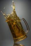 El vidrio de cerveza fresca cayó en una superficie reflexiva Fotografía de archivo libre de regalías
