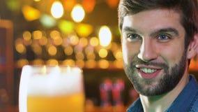 El vidrio de cerveza sonriente del hombre que tintinea caucásico en el pub, igualando el tiempo libre, se relaja almacen de video