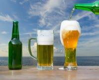 El vidrio de colada de cerveza de la botella en el mar ajardina foto de archivo libre de regalías