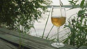 El vidrio de Emty se llena del vino blanco El vidrio está en el embarcadero de madera viejo en el lago almacen de video