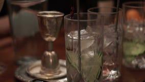 El vidrio de jarabe gotea en las tazas de cristal con un cóctel Preparación del cóctel en barra metrajes