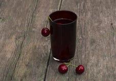 El vidrio de jugo adornado con las bayas de la cereza dulce roja Foto de archivo