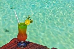 El vidrio de la bebida está en una tabla de la playa Imagenes de archivo