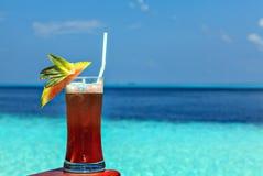 El vidrio de la bebida está en una tabla de la playa Fotos de archivo