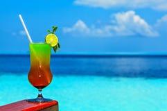 El vidrio de la bebida está en una tabla de la playa Imágenes de archivo libres de regalías