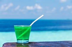 El vidrio de la bebida está en una tabla de la playa Fotos de archivo libres de regalías