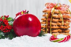 El vidrio de la Navidad de rojo reflexionó sobre el vino en la tabla con los palillos de canela, ramas del árbol de navidad, niev Fotografía de archivo