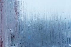 El vidrio de la ventana con la condensación, humedad fuerte, alta en el cuarto, las gotitas de agua grandes fluye abajo de, tono  Imagen de archivo