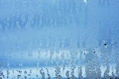 El vidrio de la ventana en el condensado en las corrientes frías del agua cae el fondo Imágenes de archivo libres de regalías
