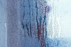 El vidrio de la ventana en el condensado en las corrientes frías del agua cae el fondo Imagen de archivo