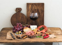 El vidrio de vino rojo, el queso y la carne suben, las uvas, higo, fresas, miel, barras de pan en la tabla de madera rústica, bla Imagen de archivo libre de regalías
