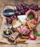 El vidrio de vino rojo, el queso y la carne suben, las uvas, higo, fresas, miel, barras de pan en la tabla de madera rústica, bla Fotos de archivo libres de regalías