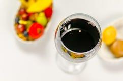El vidrio de vino rojo fino en el fondo coloreó el postre Imagen de archivo