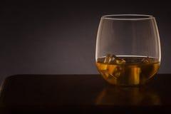 El vidrio de whisky hizo excursionismo en un fondo oscuro Foto de archivo libre de regalías
