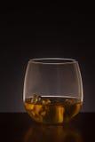 El vidrio de whisky hizo excursionismo en un fondo oscuro Fotografía de archivo libre de regalías