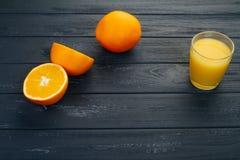 El vidrio de zumo de naranja en la tabla de madera, en la madera planta el fondo, la bebida fresca Foto de archivo