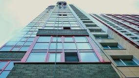 El vidrio del lapso de tiempo en un edificio alto, dos hombres lava las ventanas en un edificio alto Visión inferior Foto de archivo libre de regalías