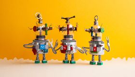 El vidrio divertido dirigió los robots del UFO en un paisaje fantástico Tres robots humanoid del juguete comunican Fondo beige am fotografía de archivo