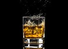 El vidrio hexagonal de brandy del whisky con hielo y salpica del hielo que cae imagen de archivo libre de regalías