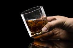 El vidrio hexagonal de brandy del whisky con hielo y salpica del hielo que cae imagen de archivo