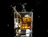 El vidrio hexagonal de brandy del whisky con hielo y salpica del hielo que cae fotos de archivo