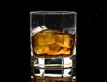 El vidrio hexagonal de brandy del whisky con hielo y salpica del hielo que cae foto de archivo libre de regalías