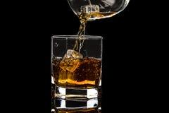 El vidrio hexagonal de brandy del whisky con hielo y salpica del hielo que cae fotos de archivo libres de regalías