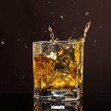 El vidrio hexagonal de whisky con hielo y salpica de un cubo de hielo abandonado y que cae fotografía de archivo libre de regalías