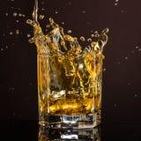 El vidrio hexagonal de whisky con hielo y salpica de un cubo de hielo abandonado y que cae imagen de archivo libre de regalías