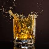 El vidrio hexagonal de whisky con hielo y salpica de un cubo de hielo abandonado y que cae imágenes de archivo libres de regalías