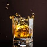 El vidrio hexagonal de whisky con hielo y salpica de un cubo de hielo abandonado y que cae fotografía de archivo