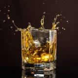 El vidrio hexagonal de whisky con hielo y salpica de un cubo de hielo abandonado y que cae fotos de archivo