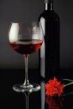 El vidrio, la botella y el rojo de vino se levantaron Imagen de archivo