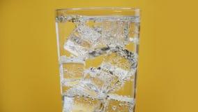 El vidrio lleno de hielo de agua chispeante cubica la bebida efervescente trasparent del fondo amarillo metrajes