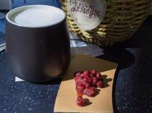 El vidrio negro se llena de leche caliente Goma dulce de la haba roja en la cartulina marrón En el fondo es una cesta de plantas  fotografía de archivo libre de regalías