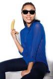 El vidrio que lleva de la muchacha hermosa con el plátano en una mano en un fondo blanco Fotografía de archivo