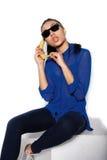 El vidrio que lleva de la muchacha hermosa con el plátano en una mano en un fondo blanco Foto de archivo