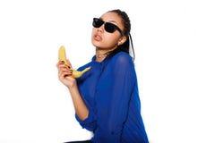 El vidrio que lleva de la muchacha hermosa con el plátano en una mano en un fondo blanco Fotos de archivo