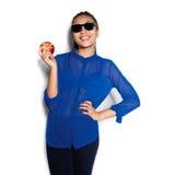 El vidrio que lleva de la muchacha hermosa con una manzana en una mano en un fondo blanco Imagen de archivo libre de regalías
