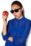 El vidrio que lleva de la muchacha hermosa con una manzana en una mano en un fondo blanco Imágenes de archivo libres de regalías