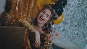 El vidrio que tintinea de la mujer alegre de champán en el partido sobre las estrellas de oro del día de fiesta hincha el fondo M metrajes