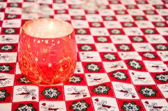 El vidrio rojo de la Navidad adornó la vela en un mantel de la Navidad Fotos de archivo libres de regalías