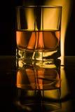 El vidrio sima-está llenando el whisky Foto de archivo