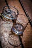 El vidrio y el cenicero vacíos del whisky con el cigarrillo se pega en la tabla de madera Foto de archivo libre de regalías