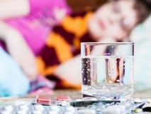 El vidrio y las píldoras en cierre de la tabla suben y mujer enferma Imágenes de archivo libres de regalías