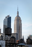 El viejo almacenamiento de madera del agua se eleva en la yuxtaposición con los rascacielos modernos como Empire State Building Imagen de archivo