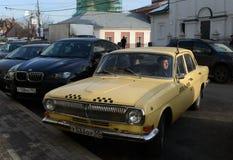 El viejo amarillo del taxi del ` de Volga del ` del coche GAZ-24 está en la calle Varvarka en Moscú Fotografía de archivo libre de regalías